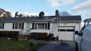 Workers repairing shingles on roof