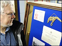 Howard Heeley looking at  a replica of a Polish pilots badge