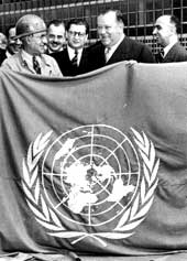 Building and administrative personnel hold the United Nations flag