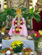 Statue of the elephant-headed Ganesh, surrounded by flowers, plants and offerings