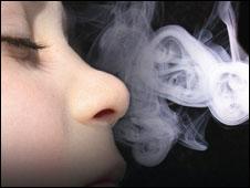 Niño aspirando humo de cigarrillo.