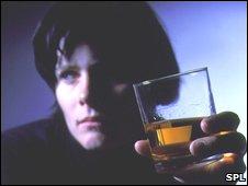 Mujer con vaso de whiskey.