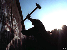A man hammering at the Berlin Wall