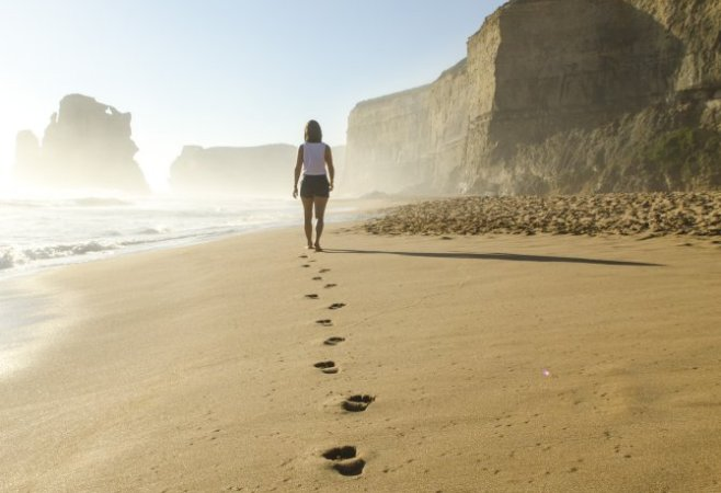 Frau geht am Strand entlang