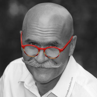 Porträt von Andreas Koller, rote Brille, Glatze, Schnauzer, weißes Hemd