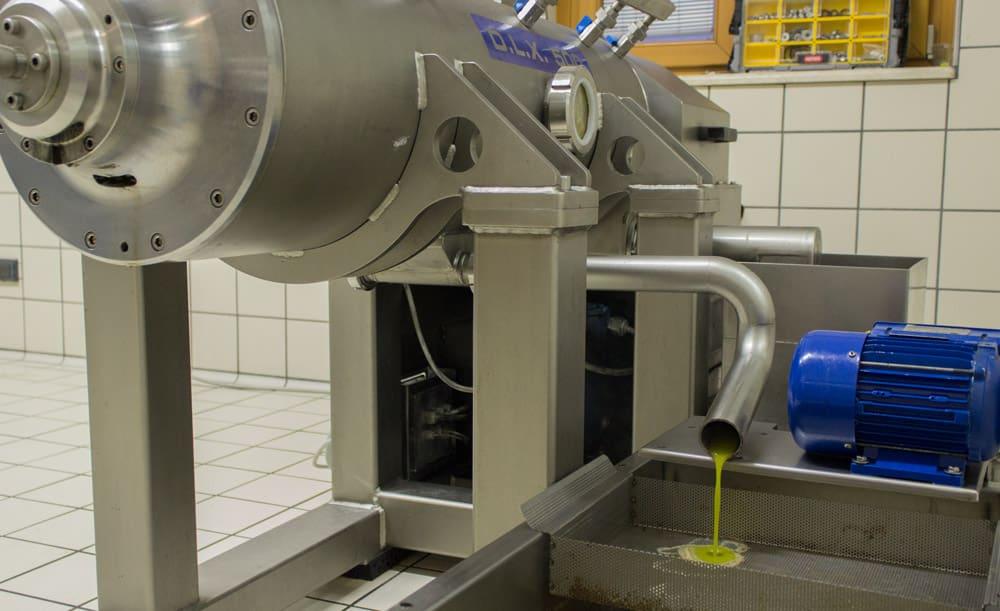 Filtrazione dell'olio appena uscito da macchinario di spremitura delle olive di Gargnagno