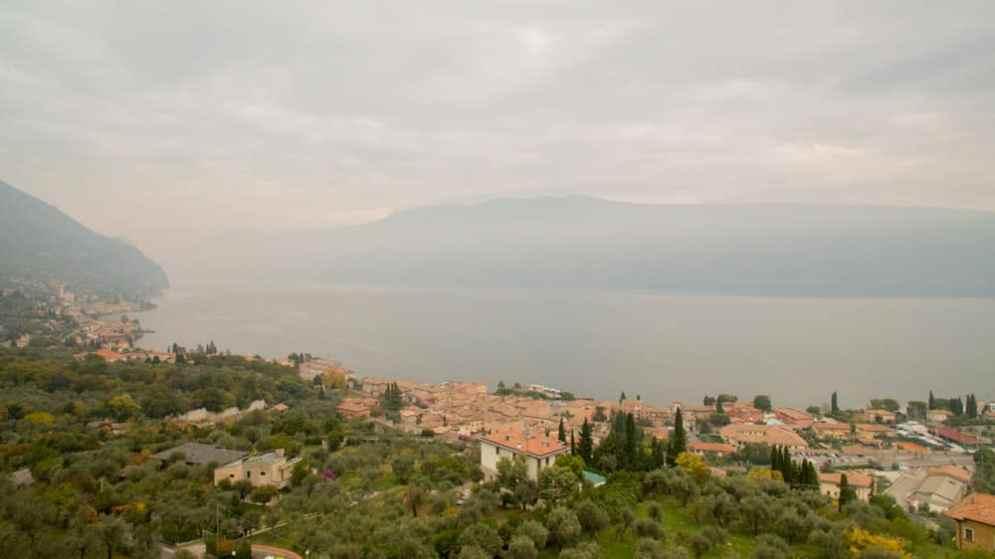 Tramonto con cielo nuvoloso sul lago di Garda con uliveti