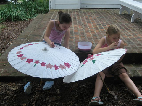 Lillian Soltys and Annie Washa take paint brushes to a pair of parasols.