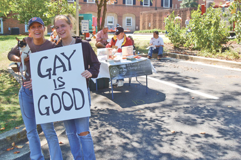 "IN JUXTAPOSITION at the Falls Church Fall Festival Saturday, Rachel Kirk and Katie Demente holding a sign used by the Parents and Friends of Lesbians and Gays (PFLAG) reading ""Gay Is Good,"" next to Greg Quinlan at a table for Parents and Friends of Ex-Gays (PFOX), which represented the opposite point of view. (News-Press photo)"