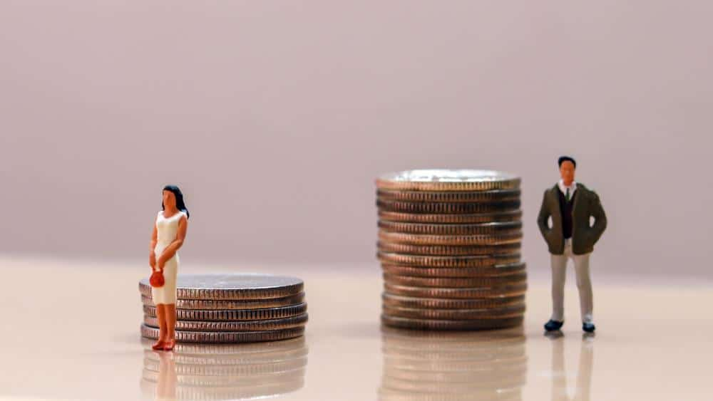 An illustration of gender discrimination, with a female in front of a small stack of coins and a male in front of a much larger stack of coins.