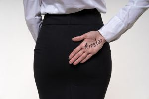 A woman has her hand behind her back with #MeToo written on her palm, indicating she has been a victim of sexual assault.