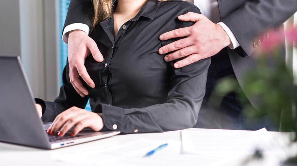 A woman is being groped by her boss at work. Sexual assault