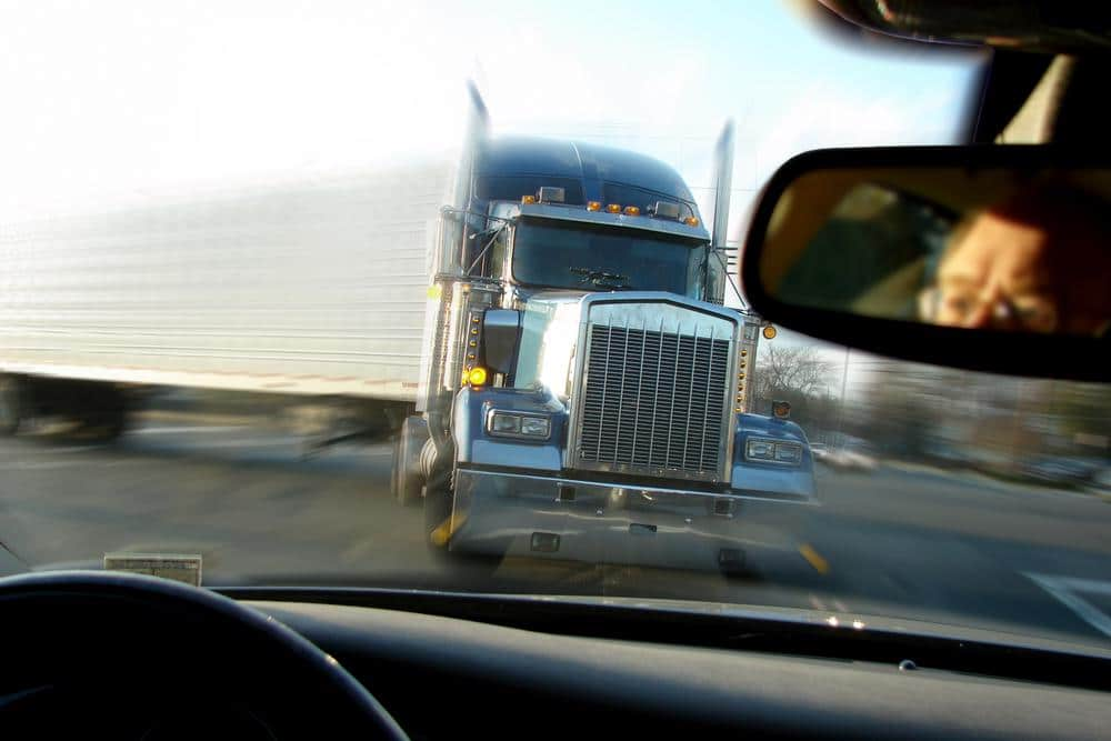 A semi-truck is about to run head on into a car, image shown from car drivers perspective.