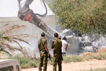 Soldiers and a settler watch as the Occupation destroys a Palestinian water tank