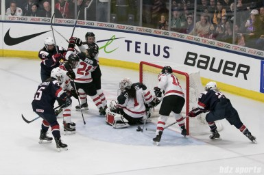 Canada's Halli Krzyzaniak #18 clears the puck off the goal line during OT.