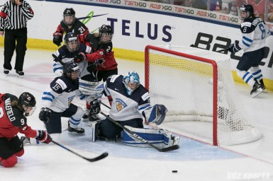 Finland's Noora Raty #41 makes the save against a shot from Canada's Jennifer Wakefield #9.