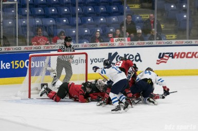 Team Canada and Finland get in a scrum in front of the Canadian goal.