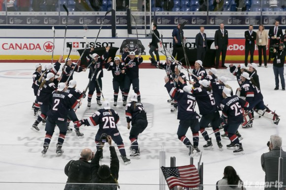 Team USA rush to center ice after their stick taps.