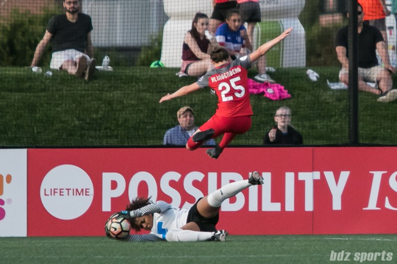 Portland Thorns FC defender Meghan Klingenberg (25) hurdles over Boston Breakers goalkeeper Abby Smith (14).