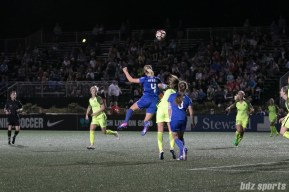 Breakers' Megan Oyster #4 heads the ball over Reign FC's Lauren Barnes #3.