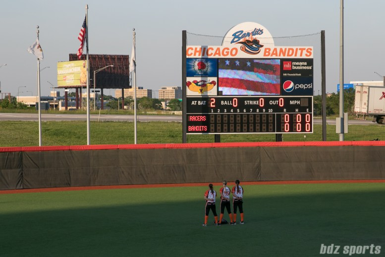 Chicago Bandits outfielders Danielle Zymkowitz (7), Brenna Moss (55), and Alexa Peterson (14) stand for the playing of the national anthem.