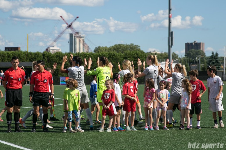 Members of the North Carolina Courage starting XI high five at the start of the game.