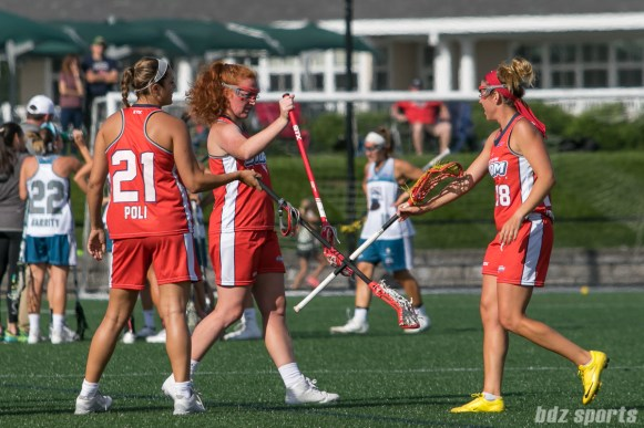 Boston Storm defender Nicole Poli (21), midfielder Hannah Murphy (8), and attacker Mckinley Sbordone (18) taps sticks.