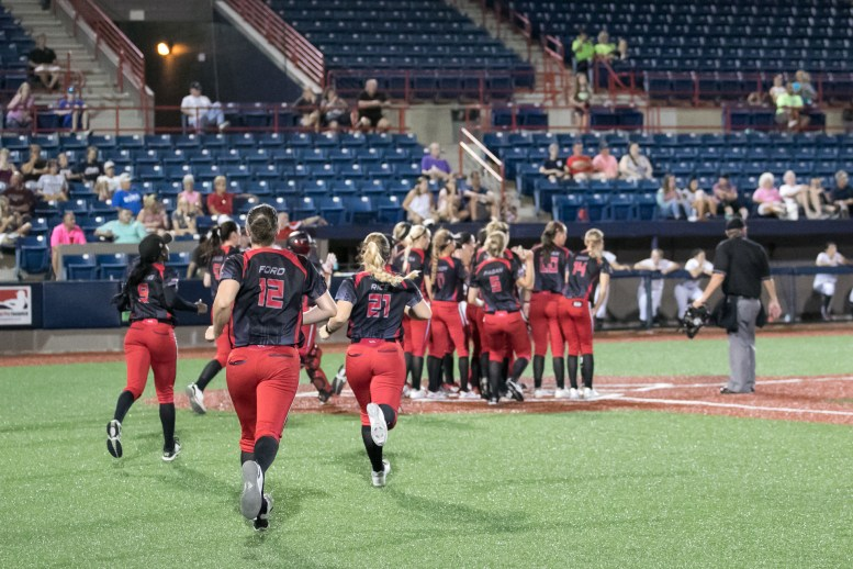 The Akron Racers bench run out to congratulate teammate Sam Fischer on her solo home run in the fourth inning.