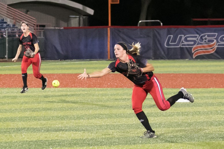 Akron Racers second baseman Ashley Thomas (1) throws underhand to get the runner out at first base.