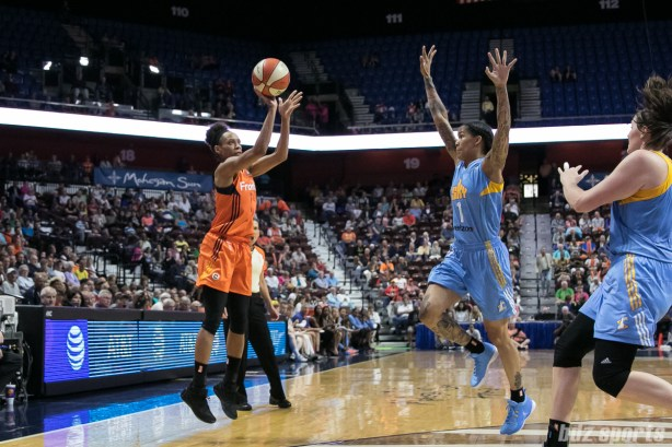 Connecticut Sun guard Jasmine Thomas (5) takes a shot as Chicago Sky forward Tamera Young (1) looks to distract her concentration.
