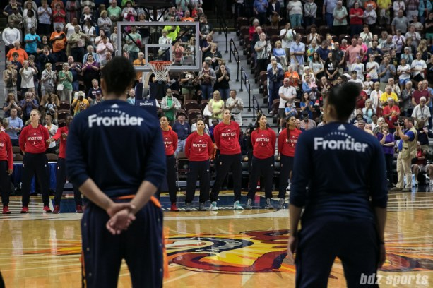 Players on the Washington Mystics face center court at the start of the game.