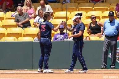 USSSA Pride outfielders Megan Wiggins (25) and Kelly Kretschman (12) bump fists as the Pride batting order is announced at the start of the game