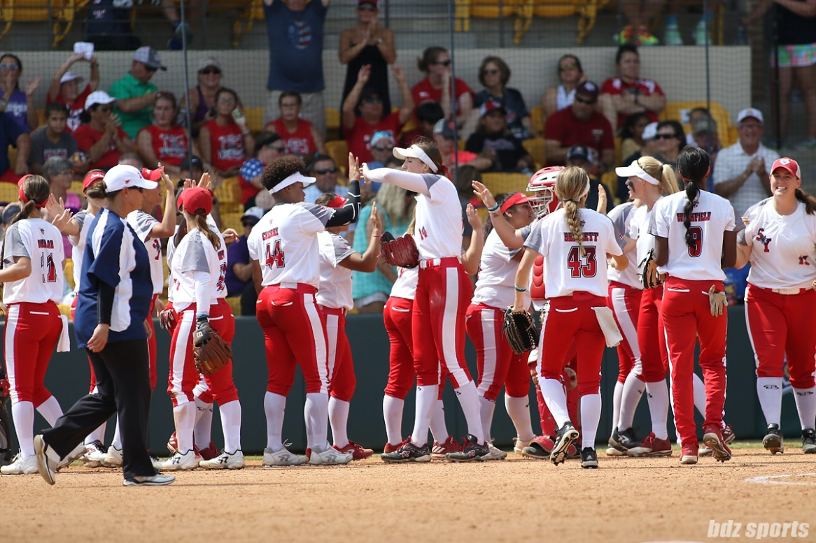 The Scrap Yard Dawgs high five each other after defeating the USSSA Pride 2 - 0 and tying the NPF Championship Final Series 1 - 1