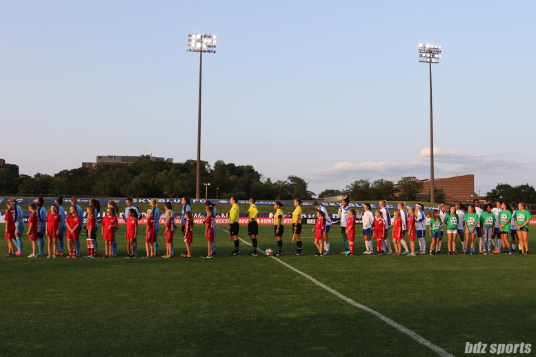 The Sky Blue FC and Boston Breakers starting XI line up for the playing of the nation anthem