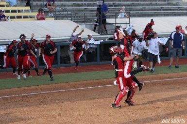 Scrap Yard Dawgs pitcher Monica Abbott (14) jumps into the arms of catcher Taylor Edwards (25) after the Dawgs defeat the USSSA Pride 5 - 2 to capture their first NPF Cowles Cup