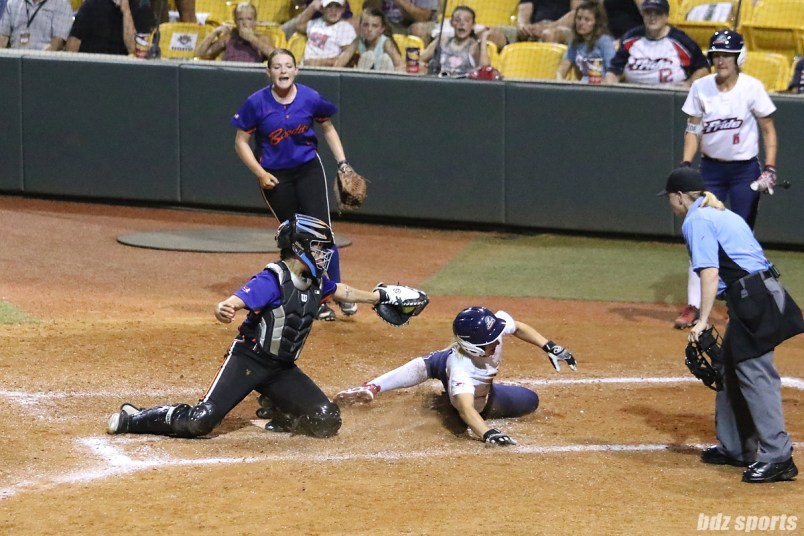 USSSA Pride first baseman Hallie Wilson (22) tries to avoid the tag from Chicago Bandits catcher Sahvanna Jaquish (33) at home plate