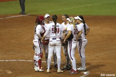 The USSSA Pride infielders huddle at the mound with one out to go in NPF Championship Game 1