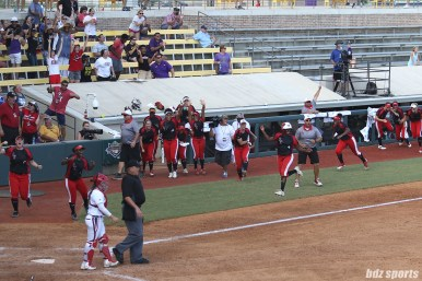 The Scrap Yard Dawgs clear the dugout and Olivia Watkins (4) runs home after teammate Kasey Cooper (not pictured) hit a two run homerun in the top of the 6th inning