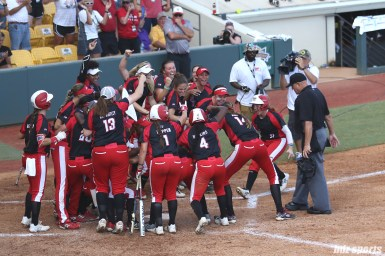 Scrap Yard Dawgs third baseman Kasey Cooper (31) runs home and is greeted by her teammates after hitting a two run homerun