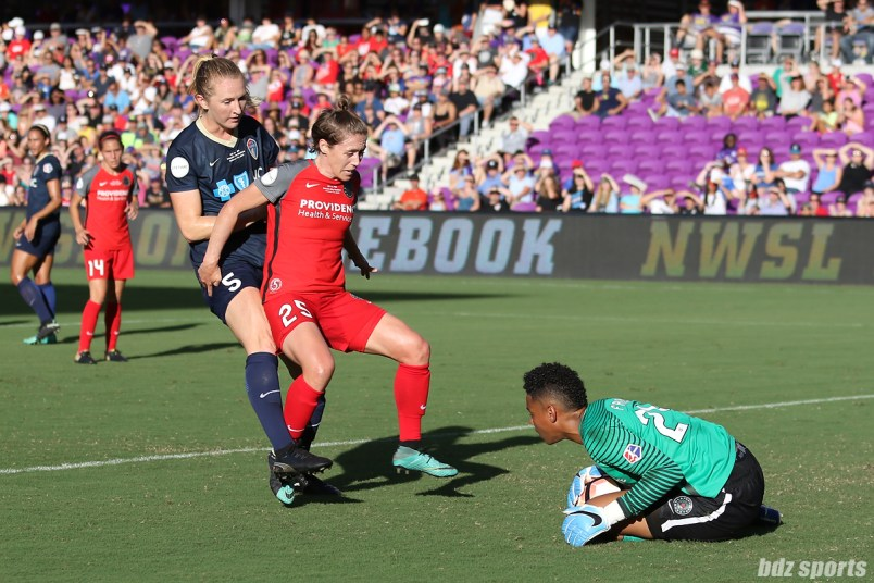 Portland Thorns FC defender Meghan Klingenberg (25) shields North Carolina Courage midfielder Sam Mewis (5) from her goalkeeper teammate goalkeeper Adrianna Franch (24)