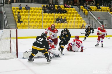 Russian team goalie Mariia Sorokina (69) smothers the puck while Boston Pride forwards Dana Trivigno (8) and Emily Field (15) apply pressure in front of the net