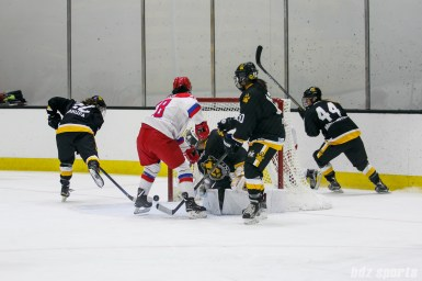 The puck is loose in front of the Boston Pride goal