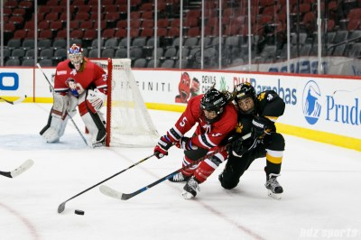 Metropolitan Riveters defender Jenny Ryan (5) looks to maintain control of the puck while Boston Pride forward Dana Trivigno (8) defends