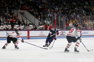 Team USA forward Meghan Duggan (10) controls the puck for Team USA