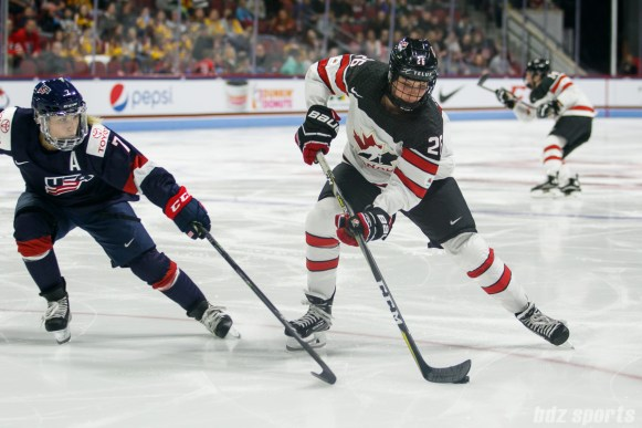 Team Canada forward Emily Clark (26) controls the puck while Team USA defender Monique Lamoureux-Morando (7) defends