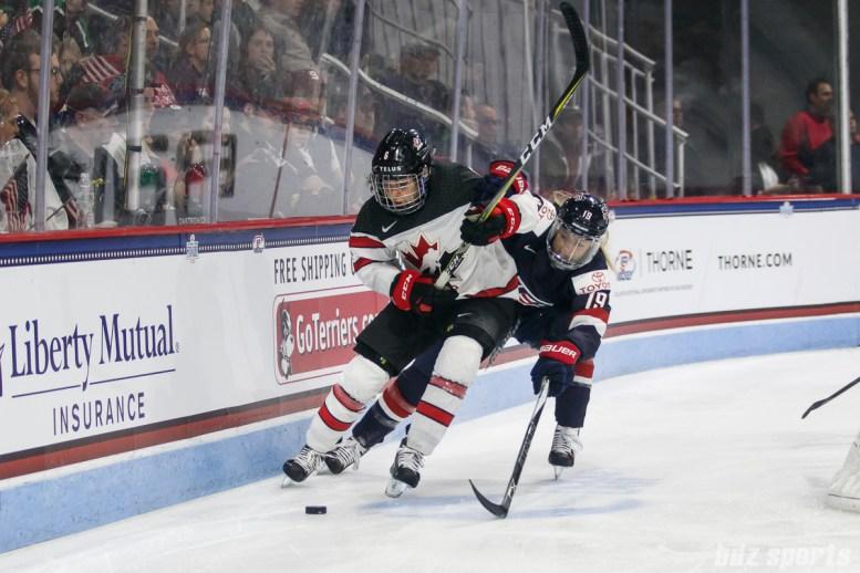 Team USA defender Gigi Marvin (19) defends against Team Canada forward Rebecca Johnston (6)
