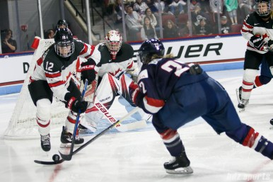 Team Canada defender Meaghan Mikkelson (12) looks to control the puck as goalie Genevieve Lacasse (31) looks on