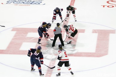 Team USA forward Kelly Pannek (12) takes the opening face off against Team Canada forward Marie-Philip Poulin (29)