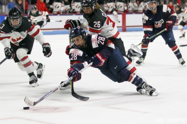 Team USA forward Amanda Kessel (28) dives to center the puck