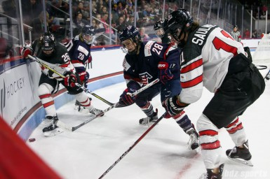 Team USA forward Amanda Kessel (28) plays the puck in the corner against Team Canada forwards Emily Clark (26) and Jillian Saulnier (11)